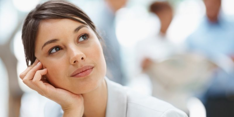 Day dreaming - Pretty Caucasian business woman with hand on chin